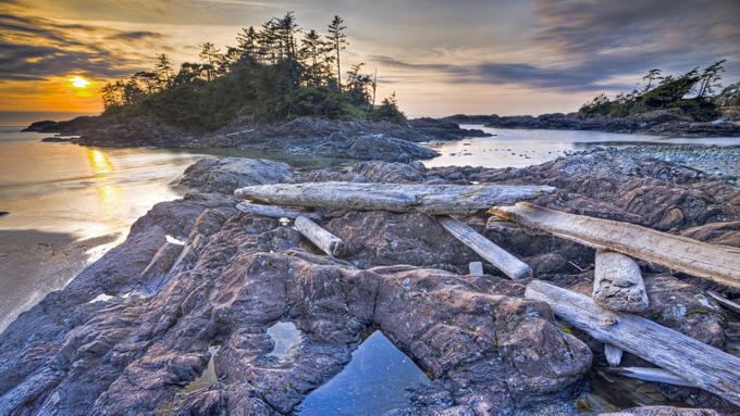 Driftwood strewn over a rocky outcrop along South Beach at sunset Pacific Rim National Park Long Beach Unit Clayoquot Sound UNESCO Biosphere Reserve West Coast Vancouver Island British Columbia Canada